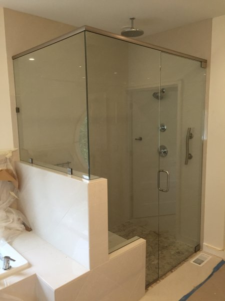 Frameless Heavy glass Door & Panel with 90 degree return with header, pivot door and panel installed with clamps