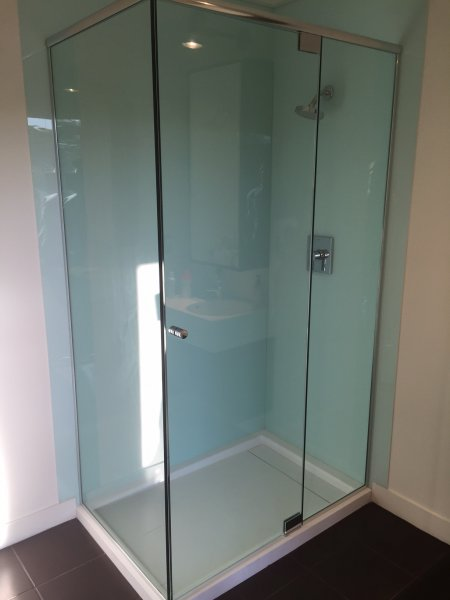 Frameless Heavy Glass Door & Panel with 90 Degree with header and panels installed with channel. Brushed Nickel clear Knob