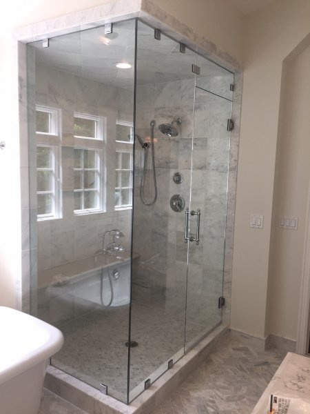 Frameless Heavy glass Door & Panel with 90 degree return installed with clamps to ceiling and operating transom. Symphony straight handle